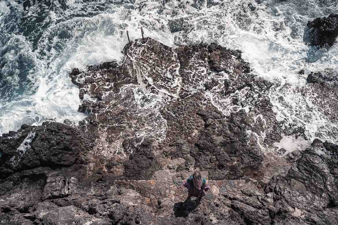 This photo shows the wild untamed sea at Portello. Maria is standing on the dark rocks facing the sea. Katerina shot this image from the walls above.