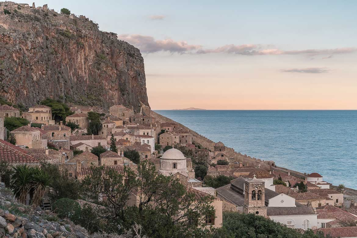This photo shows the Lower Town with the rock looming above it and the calm blue sea at sunset.