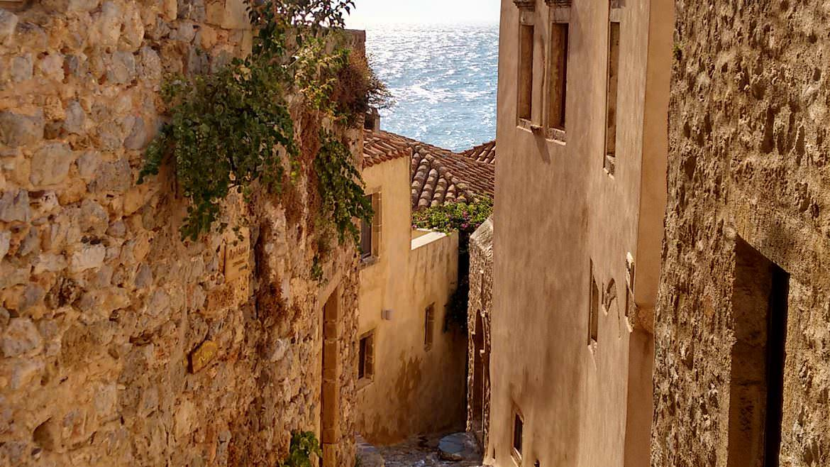 This photo shows a narrow cobblestone street inside the castle of Monemvasia in the summer with the sea glistening in the background. Monemvasia Castle Travel Guide.