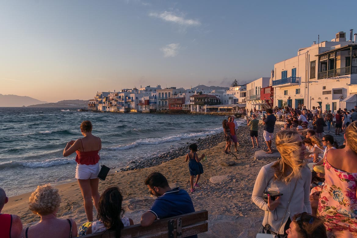 This image shows many people on the beach watching the sunset at Little Venice.