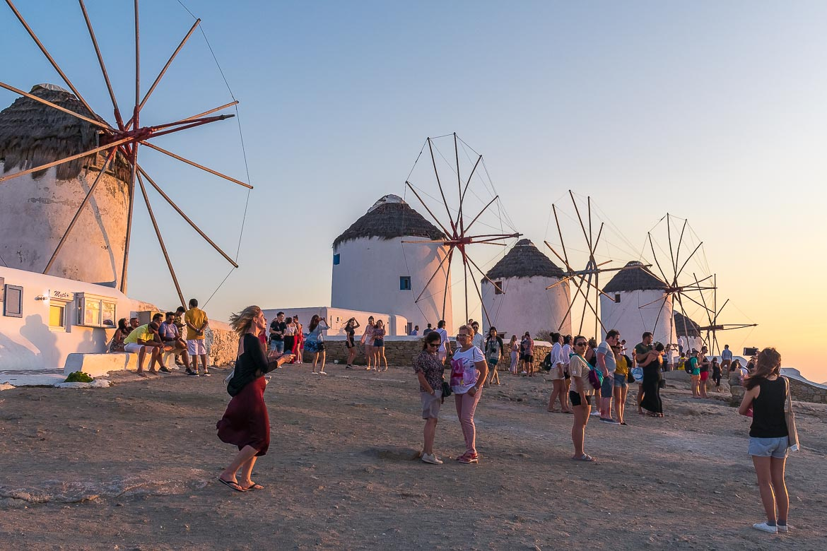 This image shows the famous windmills in Mykonos during sunset. There are many people taking in the beauty of the moment. This is the featured image of our article: Mykonos Budget Tips: A Cost-conscious Vacation Guide.