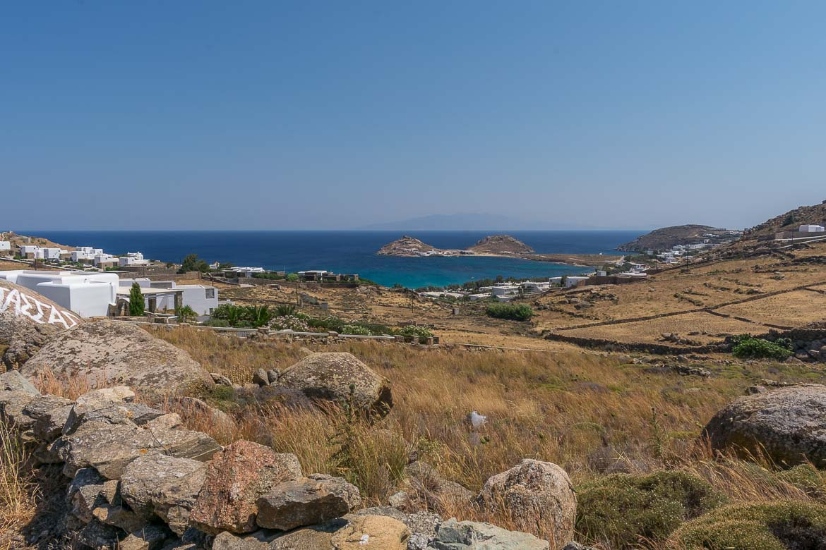 This is a panoramic shot of the countryside somewhere in Mykonos with the sea in the background.