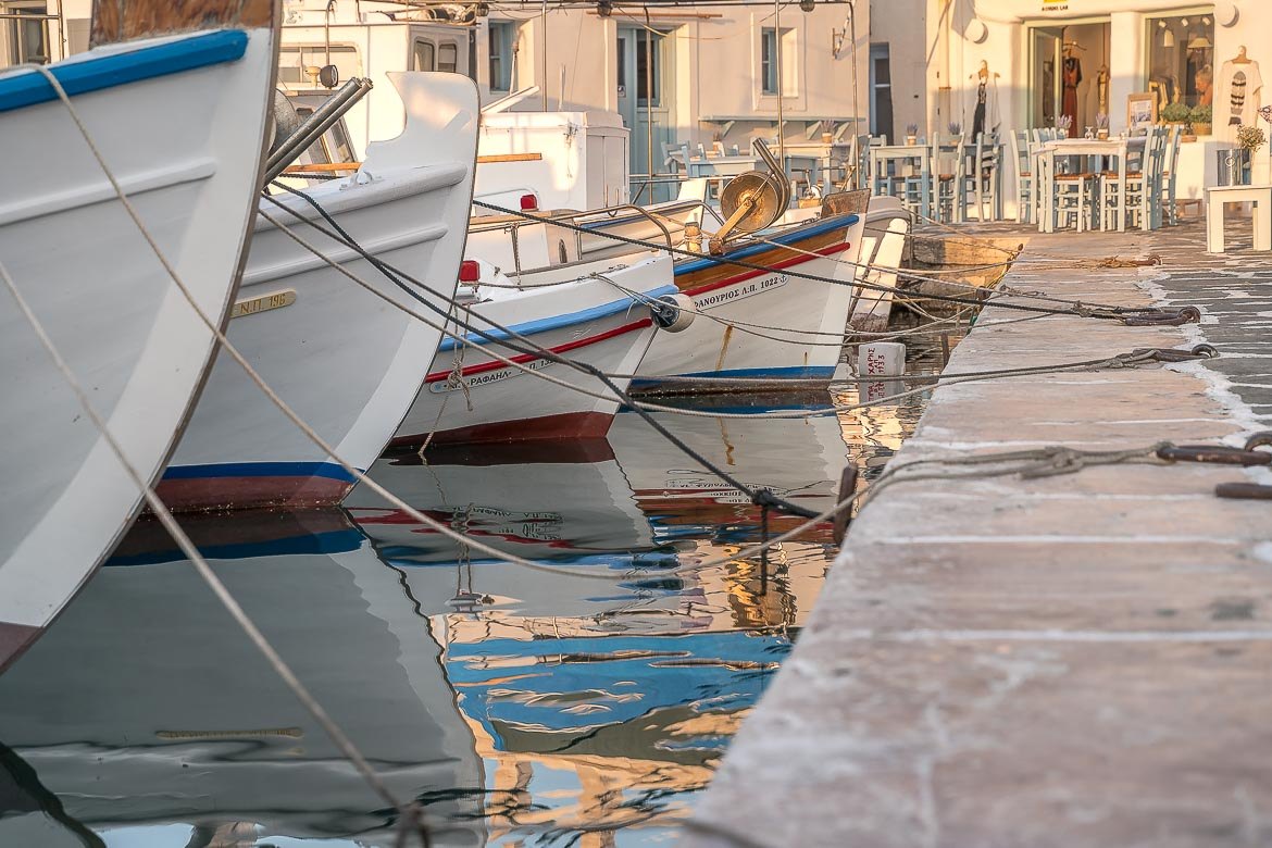 This is a close up of a line of traditional boats resting on the calm waters of Naoussa Old Port.