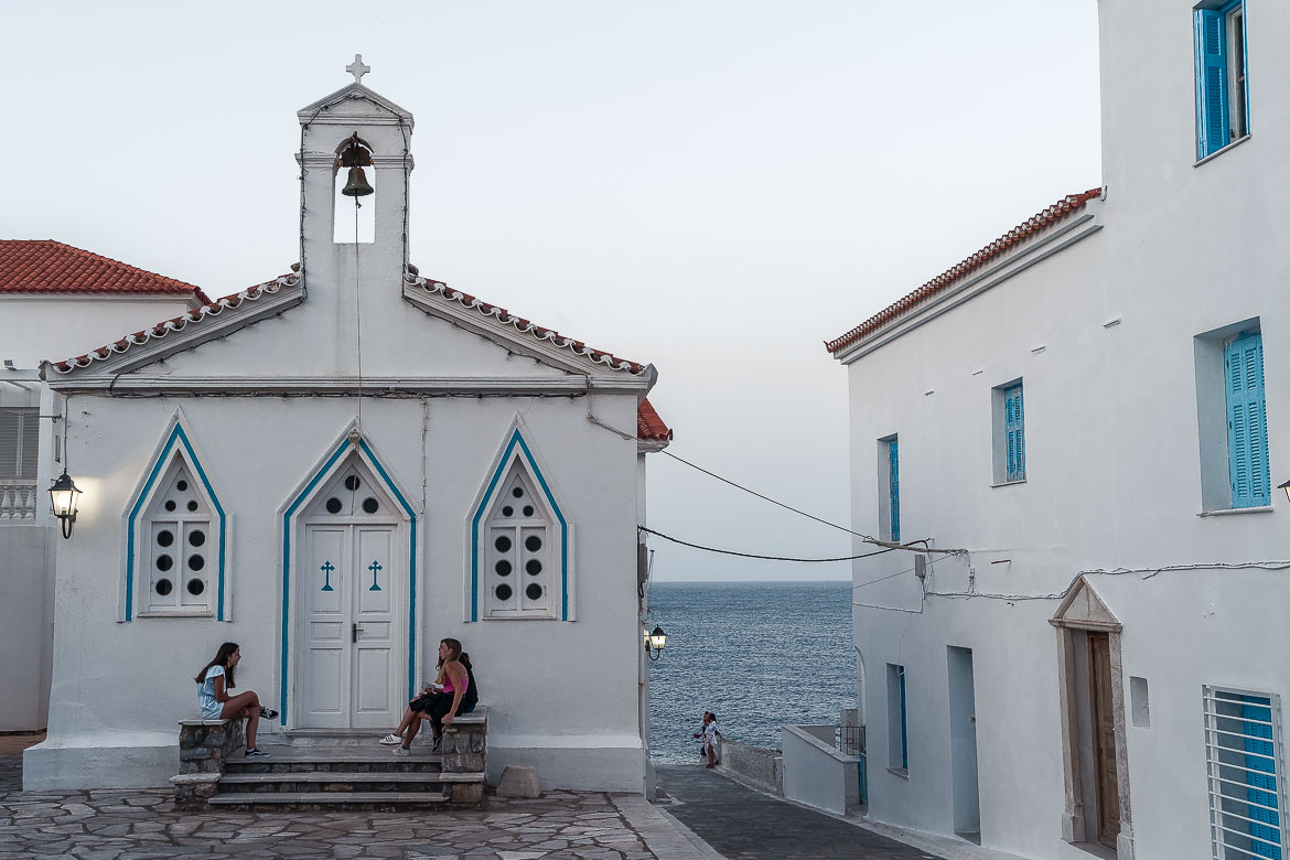 This image shows Chora in Andros. There's a whitewashed church and three girls are sitting at the stone steps chatting.