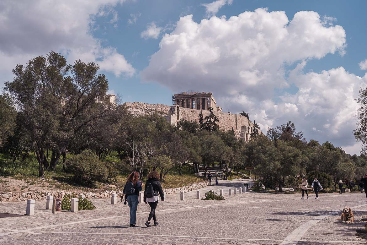 This image shows the Acropolis of Athens under a gloriously cloudy sky as seen from the gorgeous pedestrianised Dionysiou Areopagitou Street.