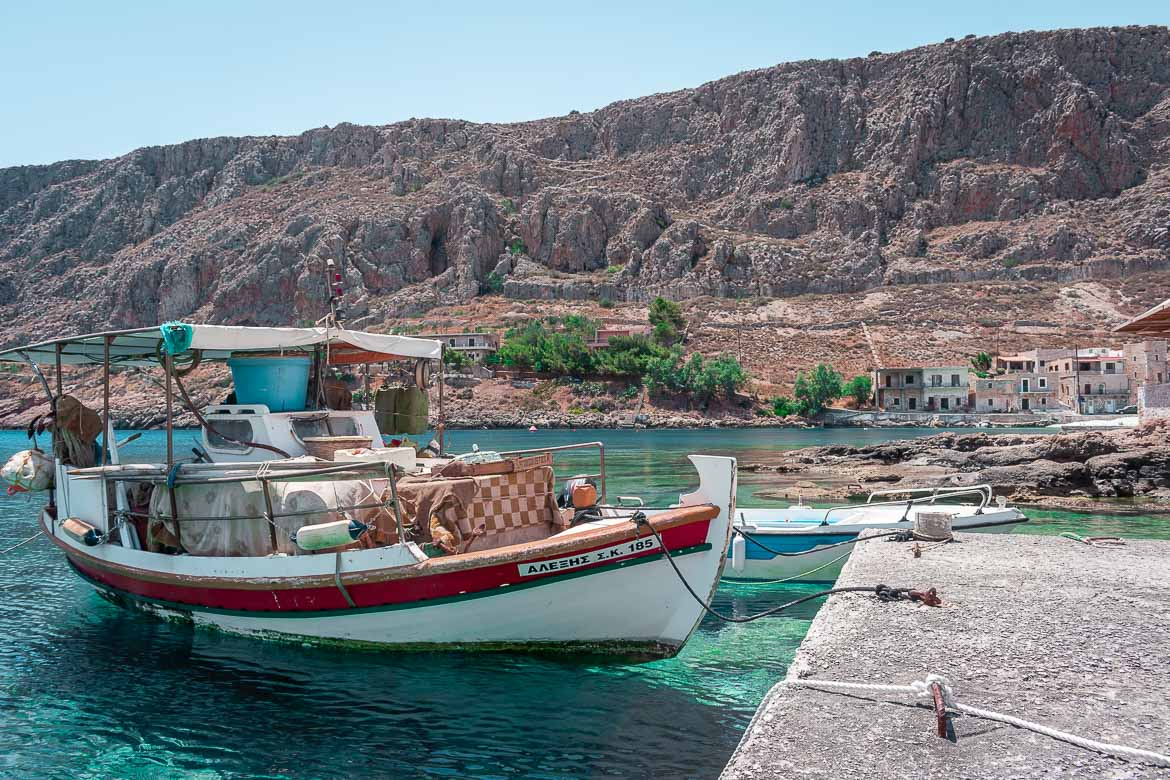 This image shows a fishing village in Mani Greece. In the foreground, a traditional fishing boat floating on calm turquoise waters.