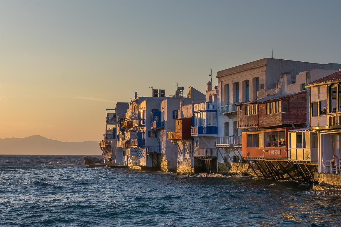 This image shows the row of buildings at Little Venice in Mykonos at sunset.