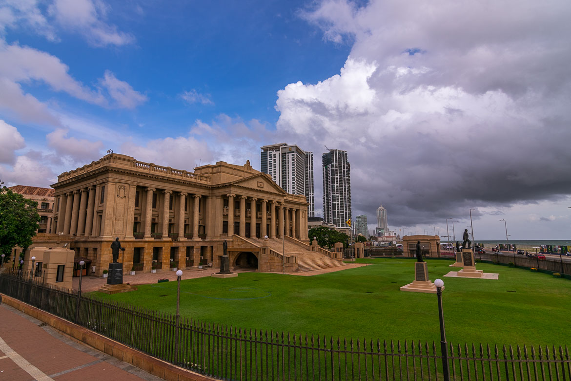 This photo shows the colonial building of the old parliament. There is fresh lawn at the front of the building. We can see modern skyscrapers in the background.
