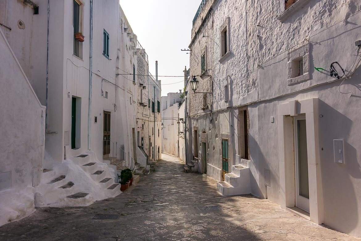 This image shows a picturesque part of Ostuni Old Town. There are old white buildings on both sides of a cobblestone street.