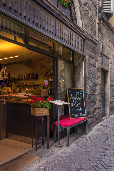 This image shows the entrance to Caffe Corsarola. There is a chalk board outside that reads: Aperitivo & Buffet €9 dalle 18:00.