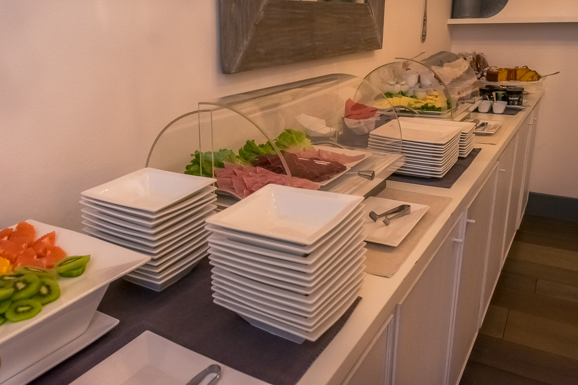 This image shows the buffet at the Gombit Hotel during breakfast. There are cold cuts, cheese, fruit, yoghurt and cake.