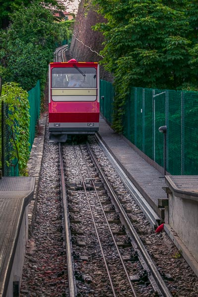 This image shows the red cabin of the San Vigilio cable car as it descends the hill towards the station.