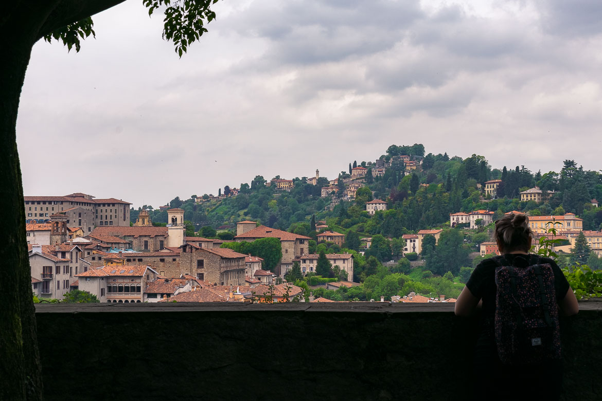 This image shows Maria with her back turned to the camera gazing at the view from Bergamo Castle.