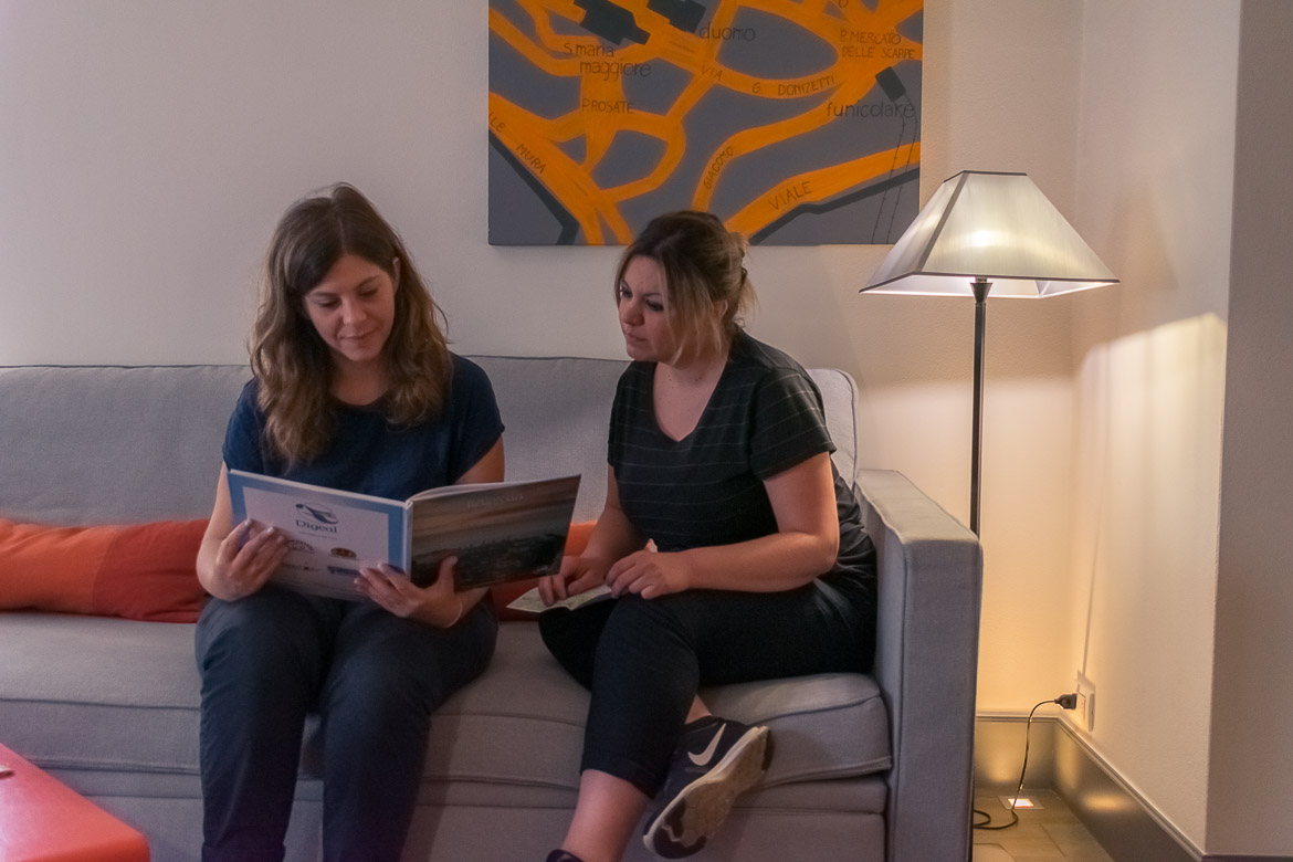 This image shows Maria and Katerina relaxing on the sofa at their room in Gombithotel. They are going over the pages of a book about the city.