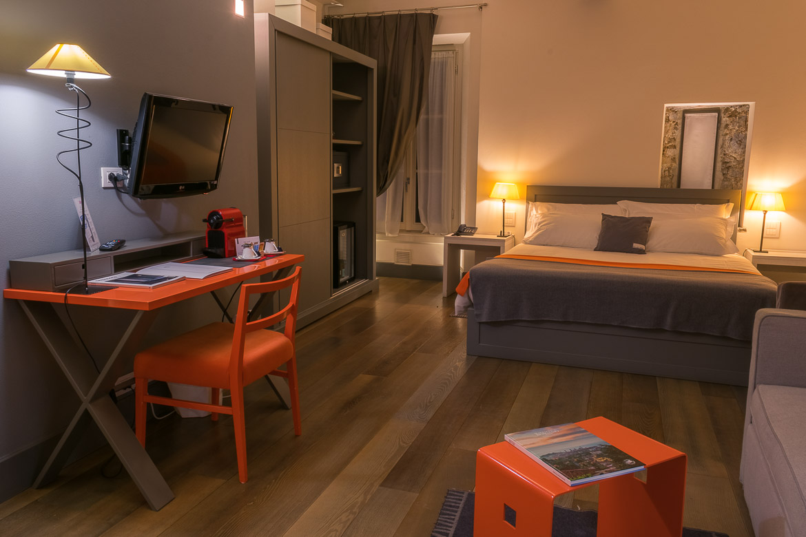 This is the room we stayed at in Bergamo. There is a large double bed, a desk with a chair and a closet. The room is decorated in grey with some touches of orange. If you are spending one day in Bergamo, Gombit Hotel is an excellent accommodation choice as it boasts a fantastic location in the heart of the Old Town.