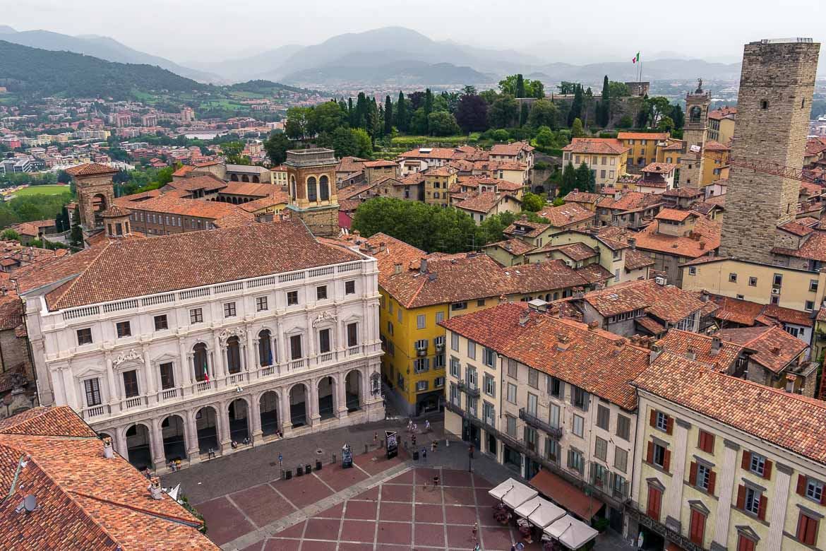 This is a panoramic view of Bergamo Old Town shot from the Civic Tower in Piazza Vecchia. We can see the Palazzo Nuovo with its exquisite white facade as well as the castle and the Gombito Tower soaring above a see of quaint red rooftops.