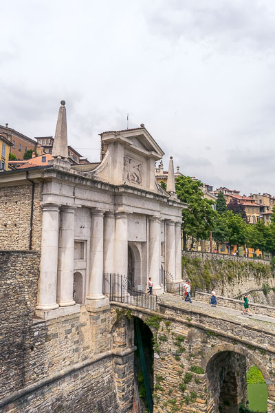 This image shows the splendid Porta San Giacomo, the most impressive gate that adorns the city walls. The facade is made of white marble and there is a stone bridge that leads to it.