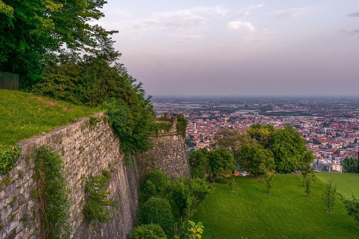 This image shows the view from San Vigilio Castle at sunset. There are many trees in the area and everything is covered in fresh green grass. In the background, views to the red rooftops of Bergamo.