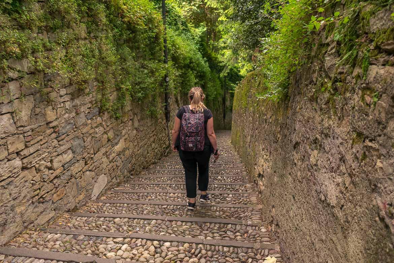 This image shows Maria descending the cobblestone steps of the Salita della Scaletta.