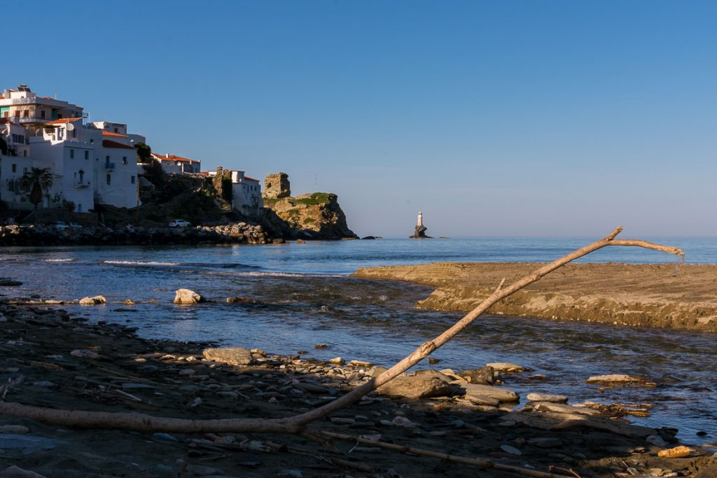 View to Chora and Tourlitis Lighthouse from Paraporti Beach. We've chosen this to be the featured image of our article 15 unique things to do in Andros Greece and full Andros Guide.