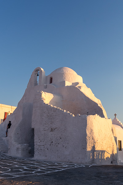 This is a close up of Panagia Paraportiani Church at sunset. The all white building has put on a pinkish golden hue from the sun.