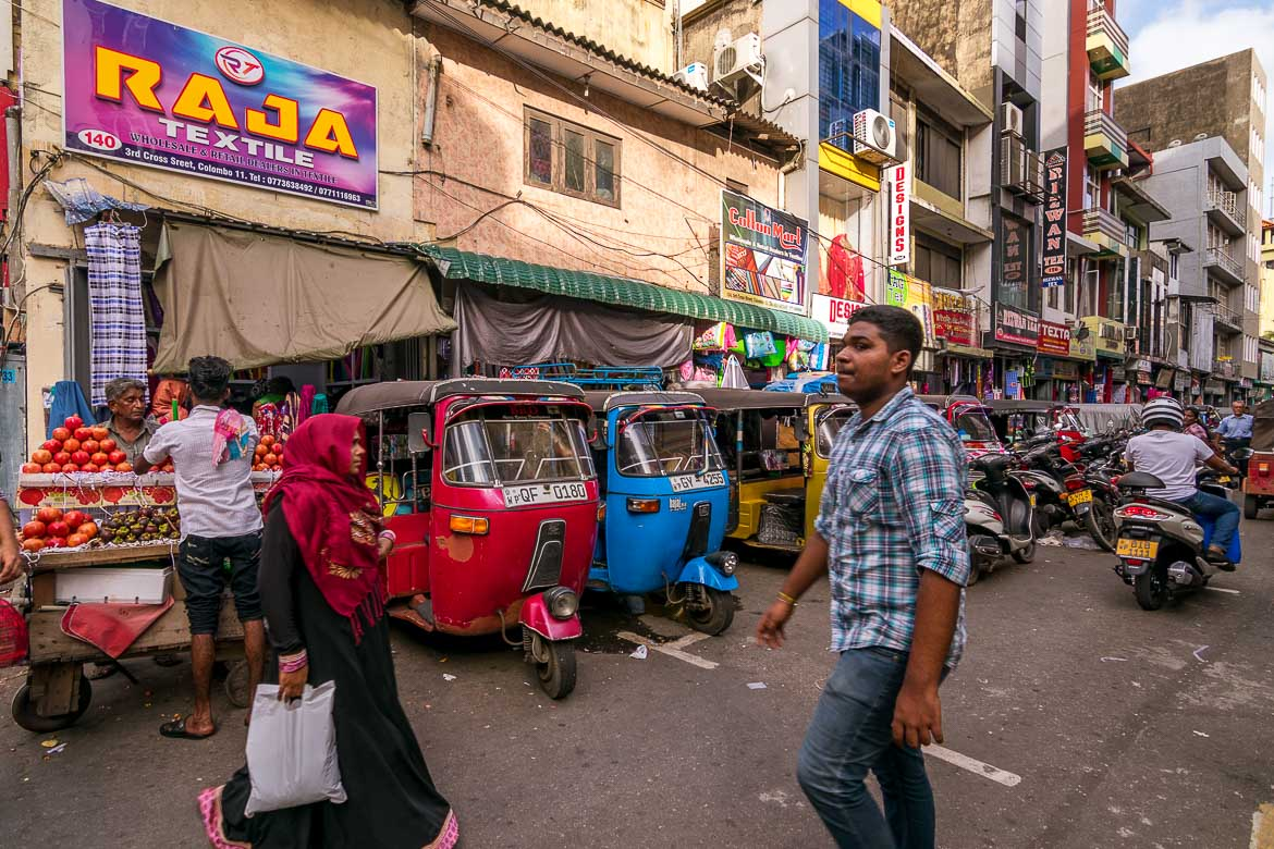This photo shows the busy streets of Pettah Market. There are tuk tuks lined on the street and people walking and shopping.