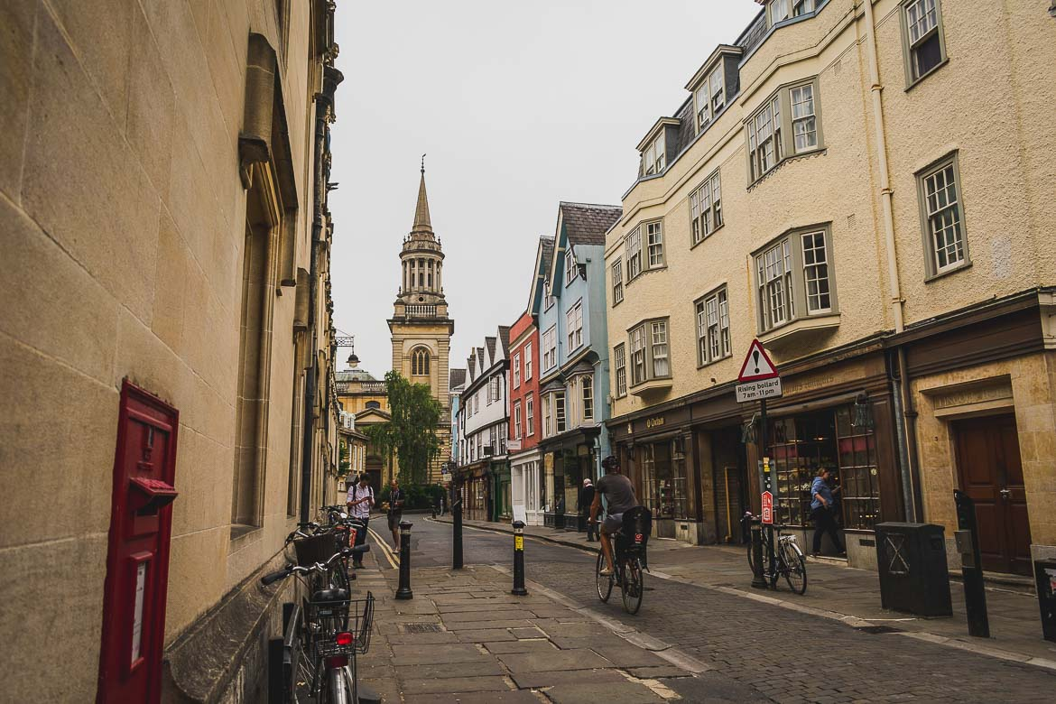 This photo shows a quaint cobblestone street in the centre of Oxford along which a lot of people walk or cycle.