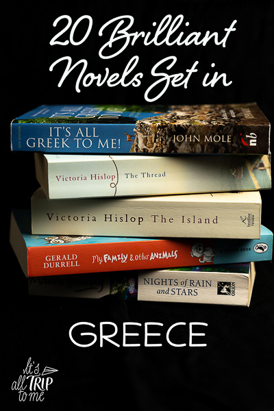 This image shows a pile of books stacked one on top of the other. This is an optimised image for Pinterest. There's overlay text that reads: 20 Brilliant Novels set in Greece. If you like our article, please pin this image!