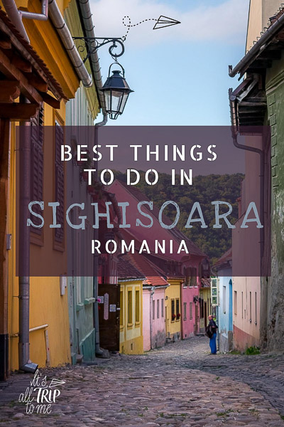 This image shows a picturesque cobblestone street within the walls of Sighisoara Citadel. The street is lined with colourful buildings. This is an optimised image for Pinterest. There is overlay text that reads: Best things to do in Sighisoara Romania.