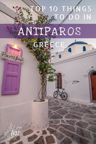This image shows a quaint street in Antiparos Town at sunrise. There is a whitewashed church with a blue dome and a bicycle resting on its wall in the background. In the foreground, we can see lilac shutters on a traditional whitewashed building. This is an optimized image for Pinterest. There is overlay text that reads: Top 10 things to do in Antiparos Greece. If you like our article, please pin this image.