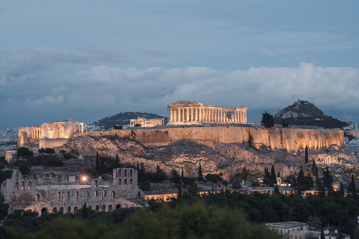 This image shows a panoramic view of the Acropolis at dusk. When planning a trip to Greece, make sure you catch the sunset at the Acropolis.