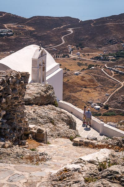 This image shows two people enjoying the view from the castle of Serifos. The photo is taken from the highest point of Chora.