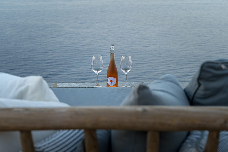 This image shows a bottle of wine with two glasses in the outdoor area of Verina Hotel in Sifnos.