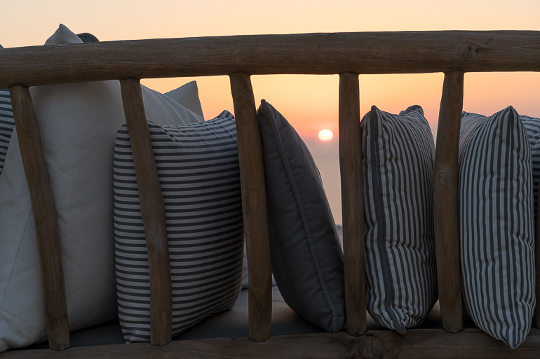 This image shows the sunset view through the pillows of a sofa from the outdoor area of Verina Hotel in Sifnos.