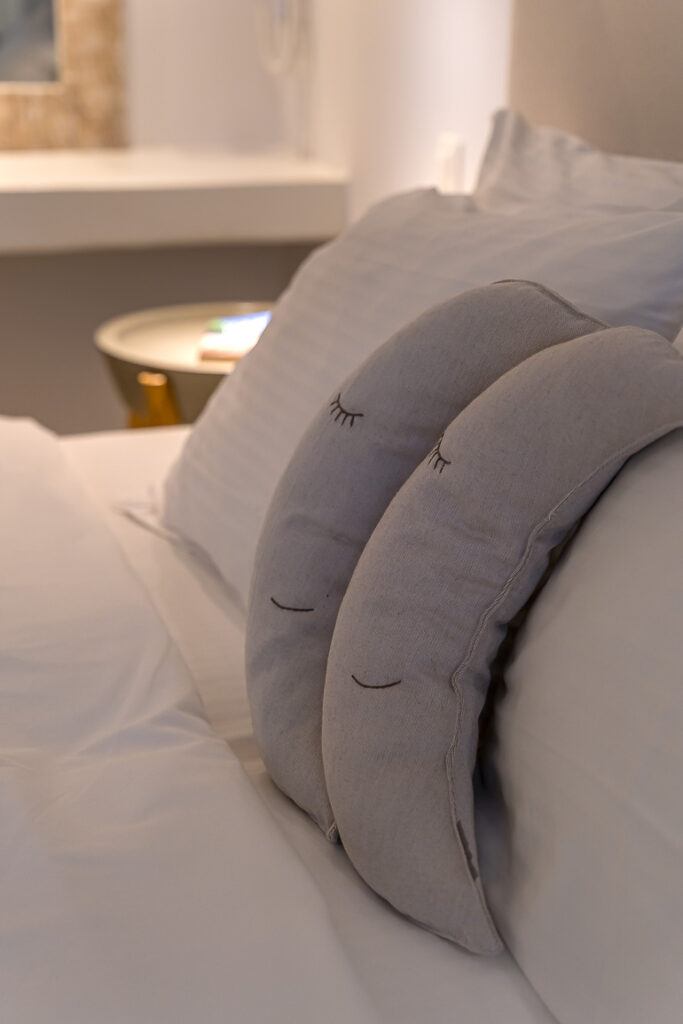 This image shows the bed pillows in a room of Adonis Hotel in Paros.