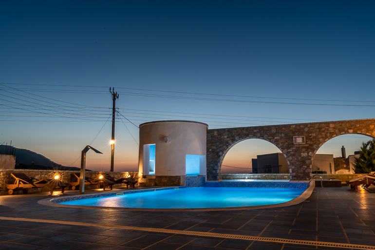 This image shows the swimming pool area of Vigla Hotel Amorgos at dusk.