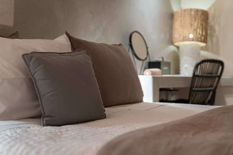 This image shows a room's bed at Verina Hotel in Sifnos.