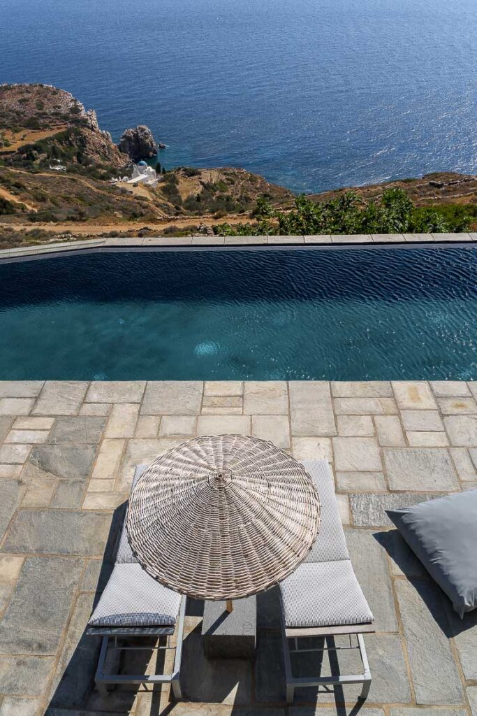 This image shows the swimming pool area of Verina Hotel in Sifnos with view to Poulati church.