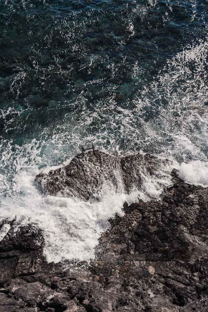 This image shows the sea waves crashing on the rocks.