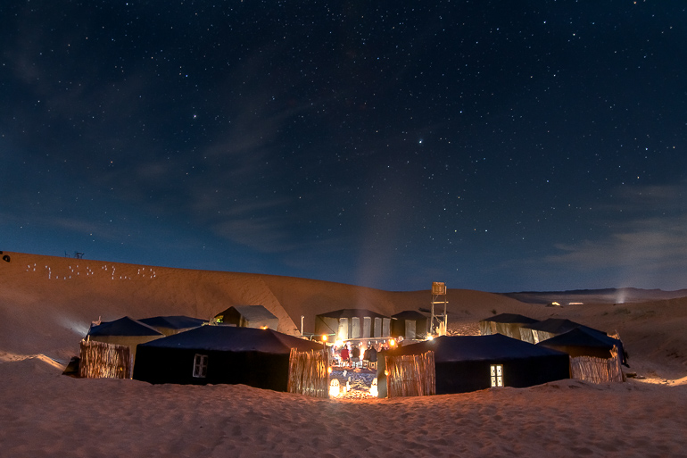 This image shows a camp in the Sahara desert on a starry night.