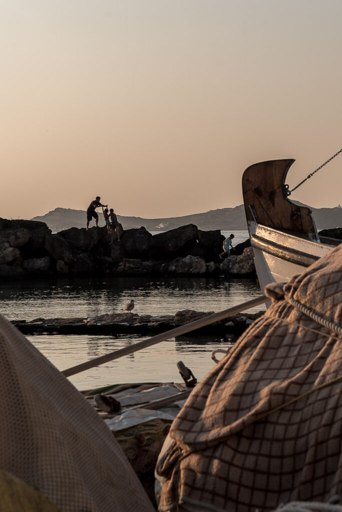 This image shows a man helping his child climb the rocks in Naoussa Paros.