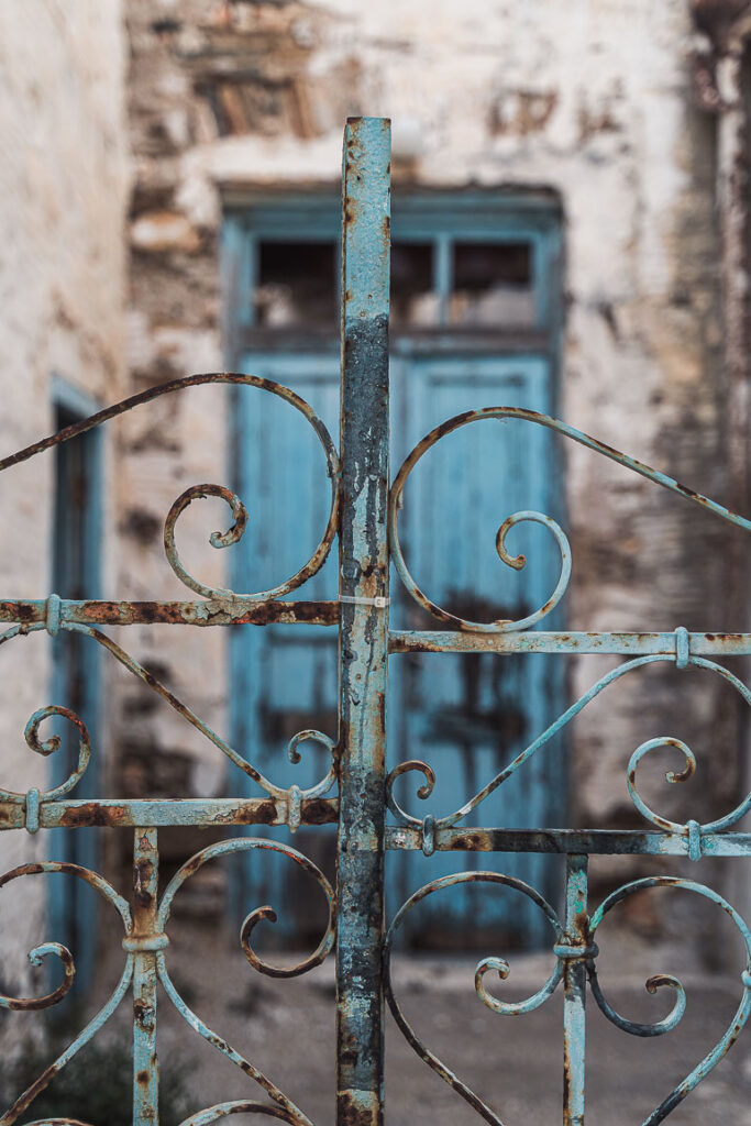 This image shows an old rusty door of an abandoned house in Paros Greece.