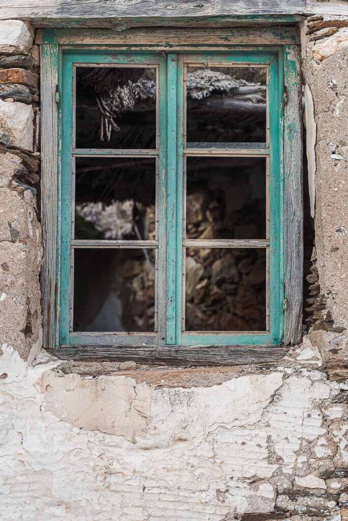 This image shows a window of an abandoned house in Paros Greece.