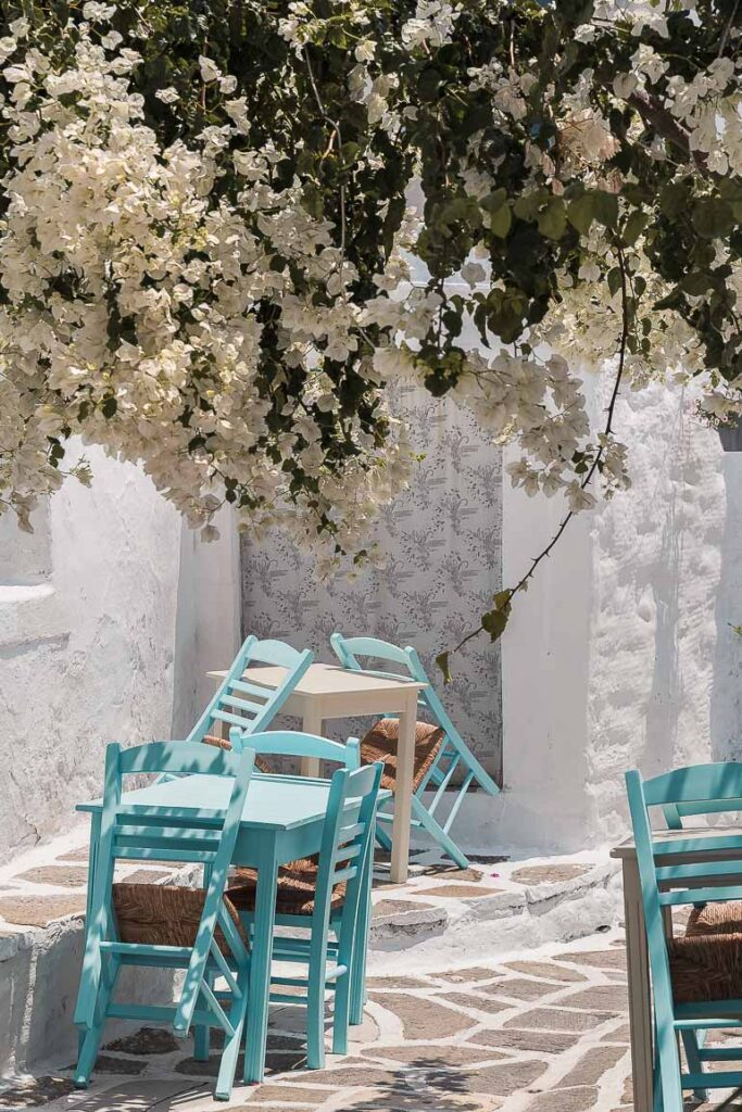 This image shows some empty tables in a traditional alley of a village in Paros.