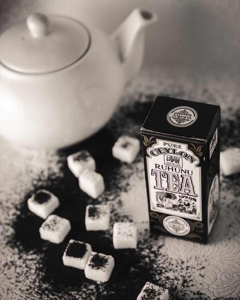 This image shows a tea package with sugar cubes and a white tea pot on its side.