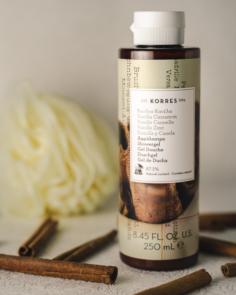 This image shows a Korres shower gel with some cinnamon sticks next to it.