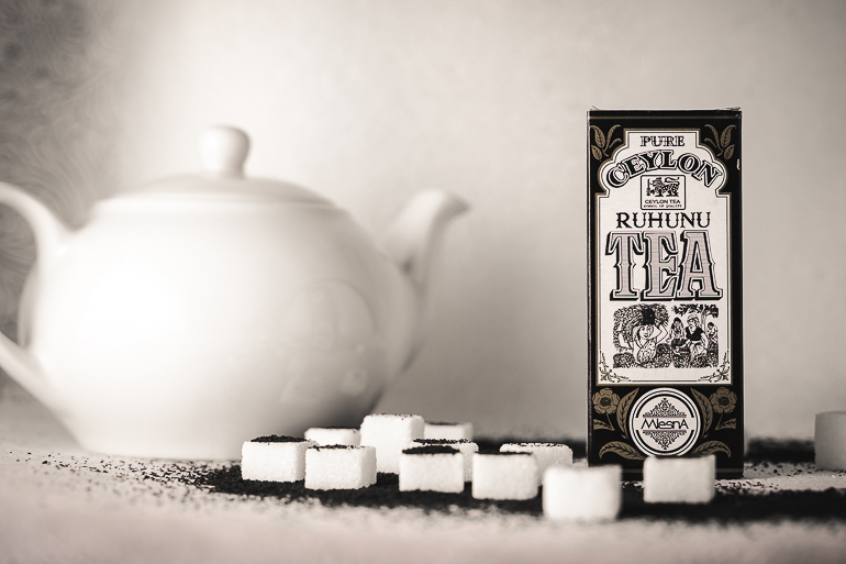 This image shows a tea package with a tea pot and a couple of sugar cubes next to it.
