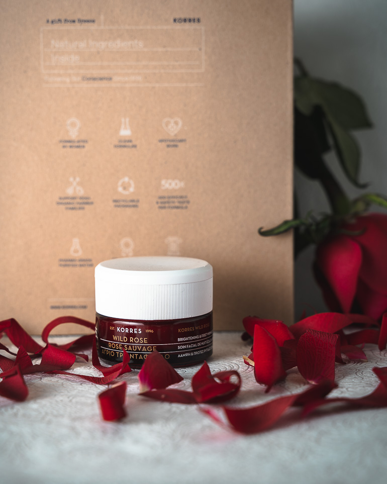 This image shows a night face cream with some red rose petals around it.