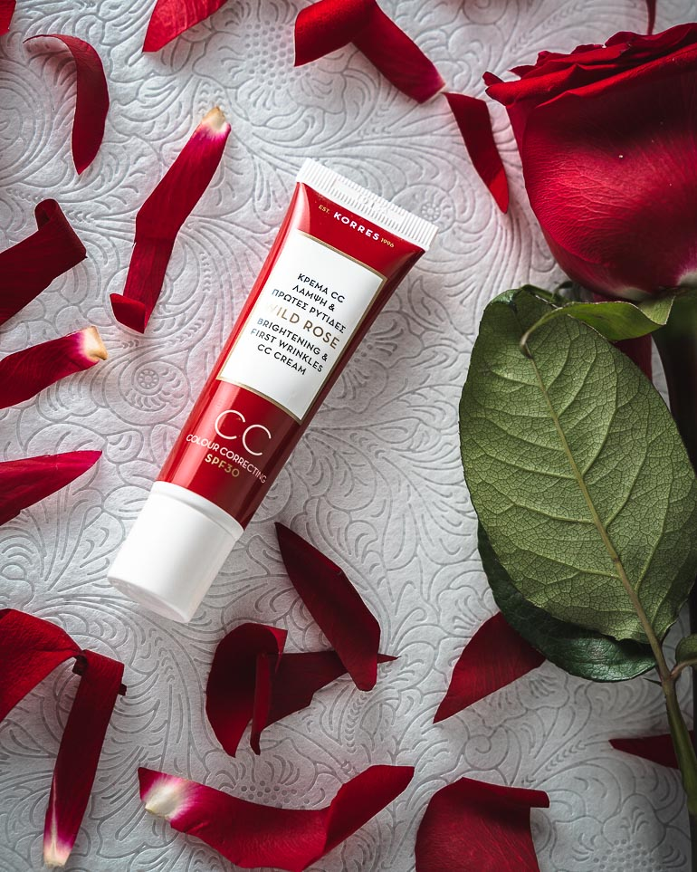 This image shows a face cream with some red rose petals next to it.