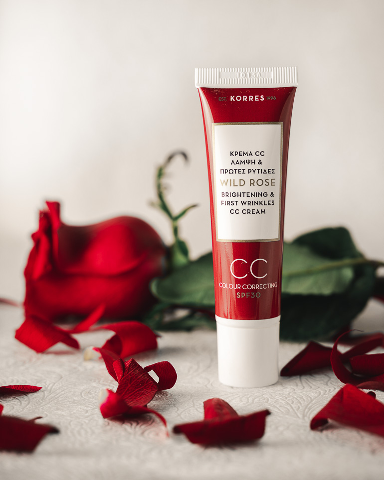 This image shows a face cream with some red rose petals around it.